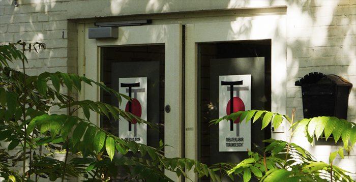 Eingang des Pavillons mit den beiden Glastüren. Dort aufgeklebt das Logo des TheaterLabor TraumGesicht. iel Raum für Ehrenamt.