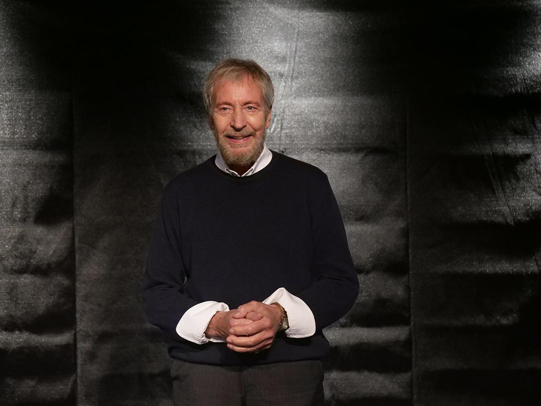 Wolfgang Keuter spricht zu teilnehmer*innen bei einm sprechtraining. Er trägt einen grauen Pulli und ein weißes Hemd.