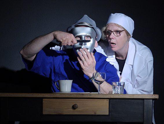 Auf der Probebühne sitzt ein Mann im blauen asiatischen Hemd an einem Tisch. Er hat eine silberne Maske auf und betrachtet sein Spiegelbild in der Klinge eines Messers. Hinter ihm steht eine Frau, in weißer Arztkleidung, und versucht die gleichen Blick staunend zu erhaschen.