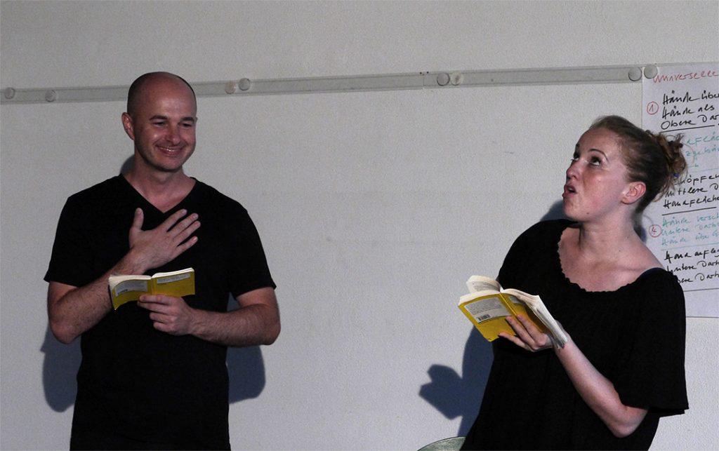 Links steht ein Mann mit Glatze und rechts eine Frau mit hochgesteckten roten Haaren. Beide tragen als Teilnehmer des Schauspielunterrichts schwarze Übungskleidung. Sie halten ein gelbes Textbuch in der Hand. Mit heiteren Gesichtern üben Sie Rollentexte.