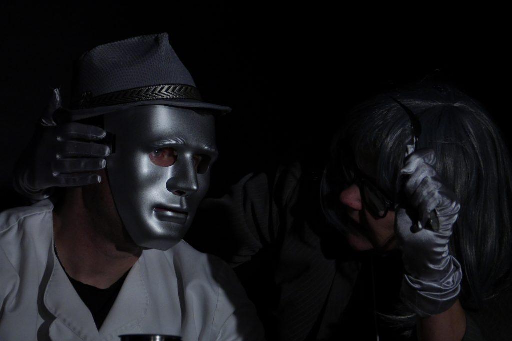 Links sitzt im schwarzen Bühnenraum ein Mann mit silberner Maske. Rechts von Ihm ein steht eine Frau gebuegt und zeigt ihm, wie man mit Messer und Gabel ist.