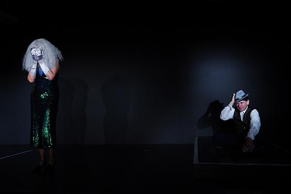 Links steht im schwarzen Bühnenraum, eine Frau mit vorm Gesicht gehaltenen Händen in silbernen Handschuhen undeinem schillernden Glitzerkleid, rechts hinten sitzt ein Mann mit silbernem Hut am Boden. Er hat ein entsetztes Gesciht.