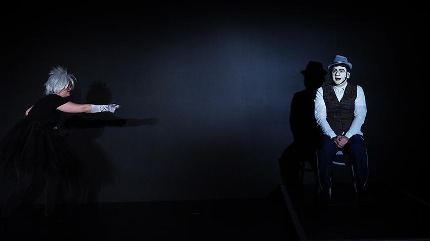 Ensemble Kaspar: Links auf der Bühnen zeigt eine junge Frau mit silbergrauen Haaren auf den Mann der rechts auf der Bühne auf einen Stuhl sitzt. Er trägt einen Hut und ist mit einer männlichen Comic-Maske geschminkt.