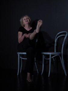Eine Frau sitzt lachend auf einem grauen Stuhl. Sie zeigt ihre rechte Fusssohle. Sie trägt schwarze Übungskleidung und befindet sich auf der Bühne.