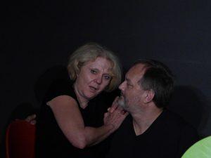 Links sitzt eine Frau und spricht mit einem Mann der rechts neben ihr auf einem Stuhl sitzt. Er hört ihr interessiert zu. Beide tragen schwarze Übungskleidung und sind auf der Bühne.