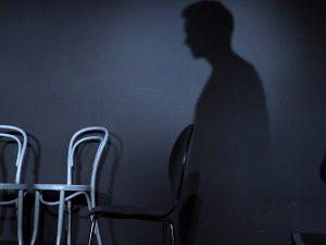 Auf der schwarzen Rückwand der Bühne zeigt sich rechts der schtten eines Mannes. Links stehen ein grauer und schwarzer Stuhl.