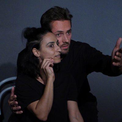 Schauspielunterricht: Ein Mann steht gebeugt seitlich neben einer sitzenden Frau. Beide schauen in die gleiche Richtung. Sie hat einen staunenden Blick und er zeigt ihr anscheinend etwas. Beide tragen schwarze Kleidung.