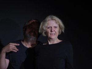 Ein Mann steht hinter einer Frau. Sie zeitgt ein entsetztes Gesicht. Beide tragen schwarze Übungskleidung und sind im schwarzem Bühnenraum.