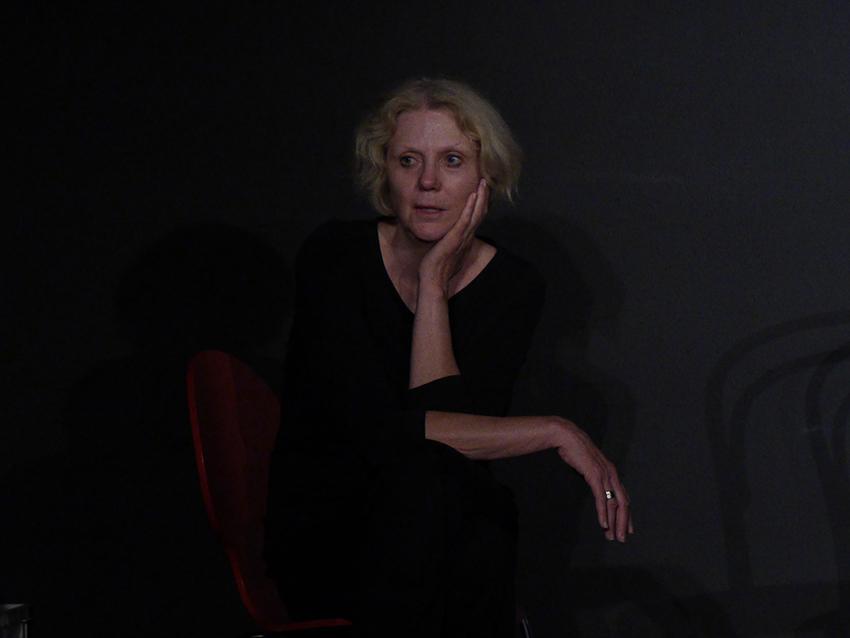 Eine Frau sitzt in schwarzer Übungskleidung mit eleganter Haltung auf eineme Stuhl auf der Bühne