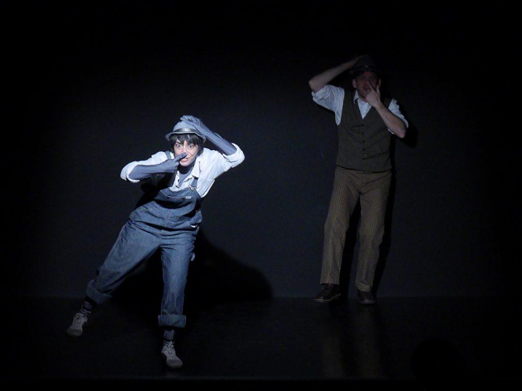 Vorne links auf der Bühne Das Kid. Es trägt eine blaue LAtzhose und einen grauen Hut. Hintenrexchts Kaspar. Er trägt eine braune Hose, ein weißes Hemd und den gleichen Hut wie das Kind