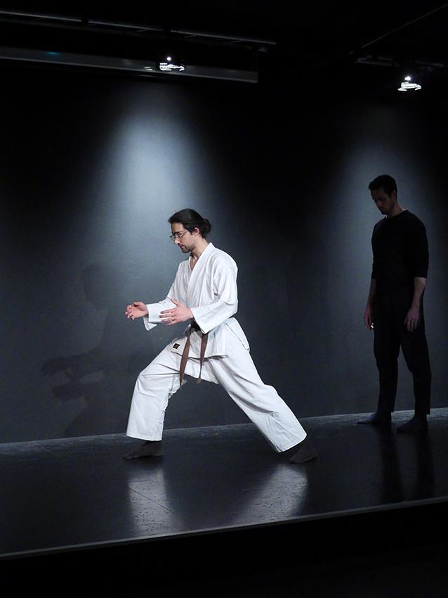 Vorne links steht ein junger Lehrer und zeigt einen Karatestand. Im Hintergrund steht ein Mann in schwarzer Übungskleidung und sieht ihm aufmerksam zu.