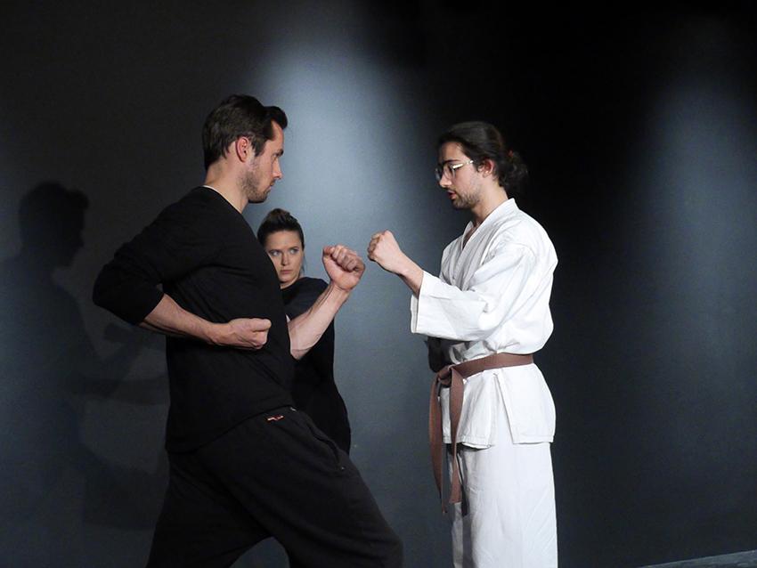 Links steht ein Mann in schwarzer Übungskleidung. Ihm gegenüber ist der Karatelehrer. Er zeigt ihm eine bestimme Haltung. Im Hintergrund schaut eine junge Frau, ebenfalls in schwarzer Übungskleidung interessiert zu.