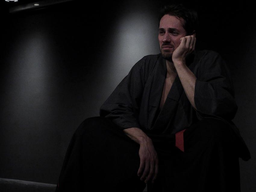 Ein junger Mann, Hisashi, sitzt am Bühnenrand und hat einen nachdenkenden Ausdruck.