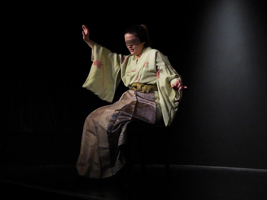 Eine junge Frau, Naoko, sitzt schwebend auf der Bühne. Sie trägt einen zitronengelben Kimono und einen Brokatrock. Sie zeigt ihre Blindheit durch tastende Bewegungen im Raum.