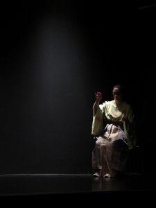 Die blinde Naoko sitzt in ihrem gelblichen und glitzernden Kimono rechts hinten auf einem Stuhl im Bühnenraum. Sie tastet vorsichtig in der Luft