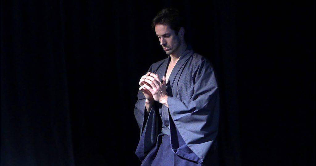 Die Figur Hisashi geht in meditativer Weise, mit gefalteten Händen von der Bühne ab.
