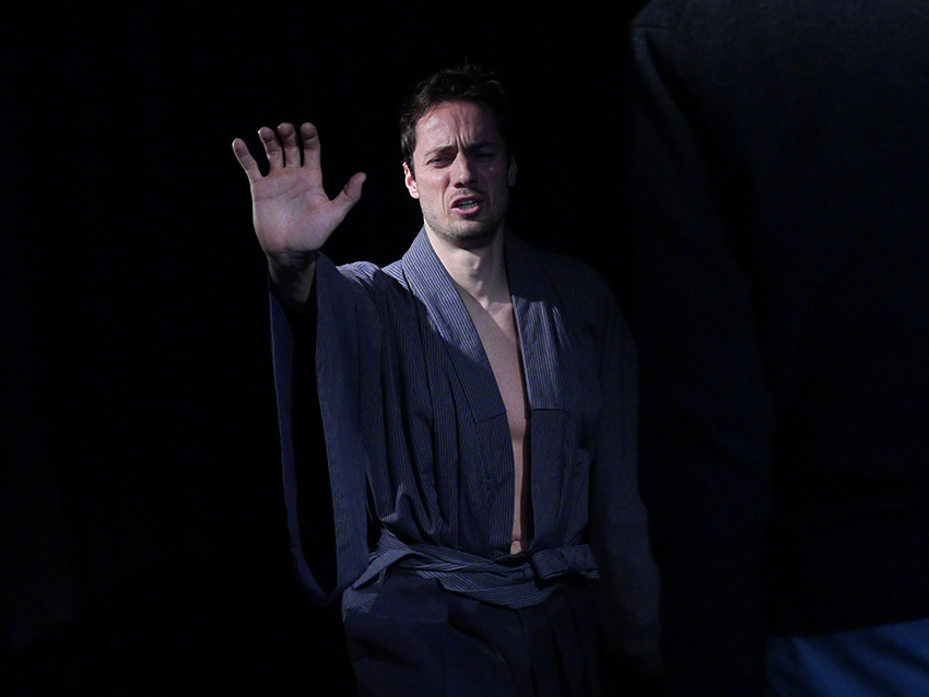 Ein junger Mann in der Rolle des Hisashi zeigt eine abwehrende Handgebärde. Er trägt einen blauen Kimono.