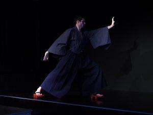 Ein junger Mann, Hisashi, steht in einem Karatestand. Er trägt einen blauen Kimono und eine blaue Hakama.