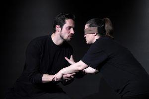 Chris hält Dinahs Hände. Sie trägt eine Augenbinde. Er ist mit seiner Aufmerksamkeit ganz bei ihr. Beide tragen schwarze Übungskleidung.