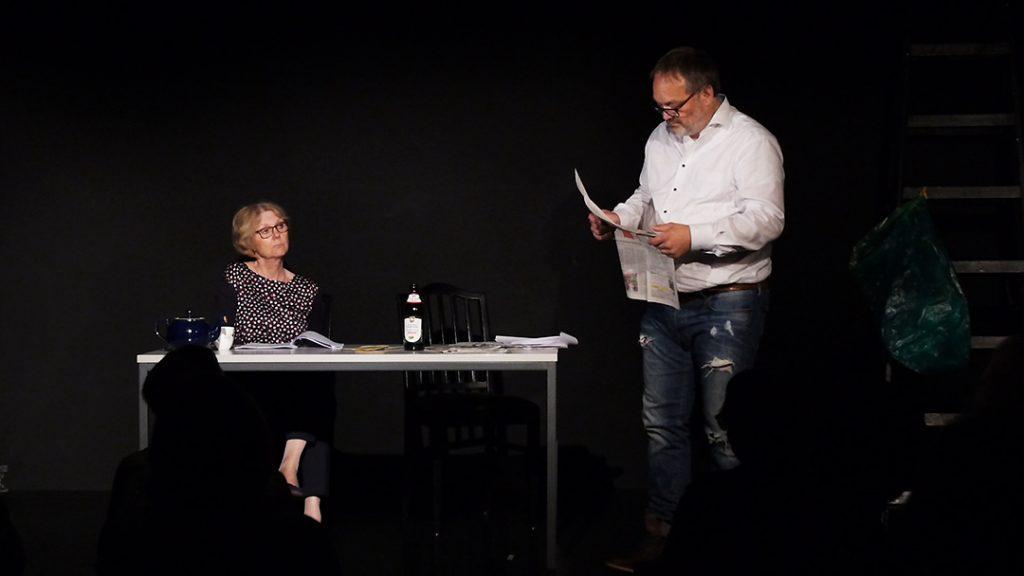 Links sitzt Lore (Sigird Abendroth) und schut in Richtung Harry (Marc Dauenhauer) er steht rechts vor dem Tisch und liest Zeitung. Die Bühne ist schwarz. Es gibt einen Tisch, zwei Stühle und einen gmütlichen Sessel auf der linken Seite.