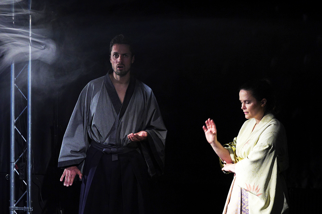 Links, Hisashi im graublauen Kimono. Er hat ein staunendes Gesicht. Rechts neben ihm steht Naoko, Sie trägt einen gelblichen Kimono und hat eine abwehrende Handgebärde.