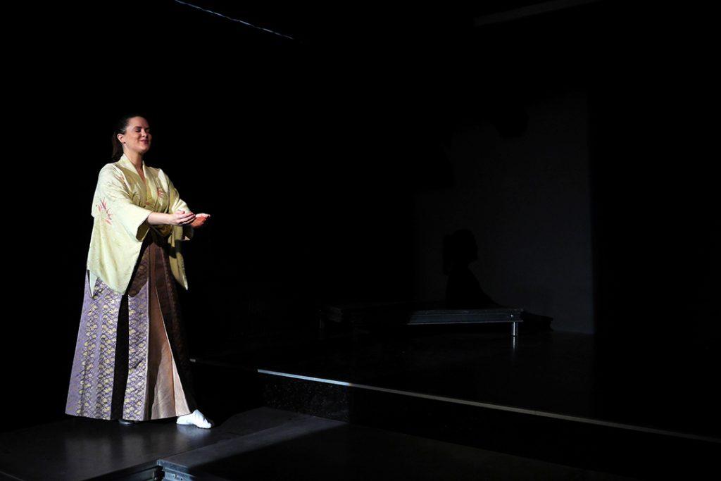 Rosei steht vorne links auf dem Bühnensteg. Sie zeigt eine schalenartige Gebärde mit geschlossenen Augen.