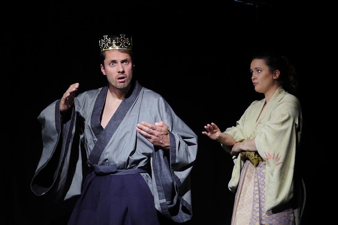 Hisashi steht links. Er trägt eine Krone. Mit fraglichem Gesichtsausdruck hört er Rosei zu. Die steht auf der Bühne seitlich hinter ihm und spricht zu ihm