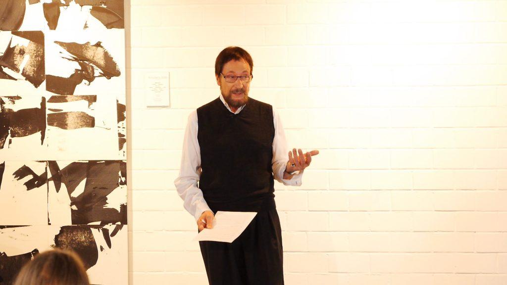 Wolfgang Keuter steht vor einer weißen Wand, links im Bild ein großes Gemälde in schwarz/weiß, und erzähl aus seinem Buch Staunen – Stopp und Stille.