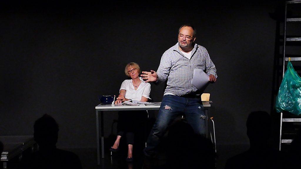 Links sitzt Lore (Sigird Abendroth) und schaut in Richtung Harry (Marc Dauenhauer). Er steht rechts vor dem Tisch und erinnert sich tanzend an das Hochzeitsfest ihrer Tochter. Die Bühne ist schwarz. Es gibt einen Tisch, zwei Stühle und einen gmütlichen Sessel auf der linken Seite.