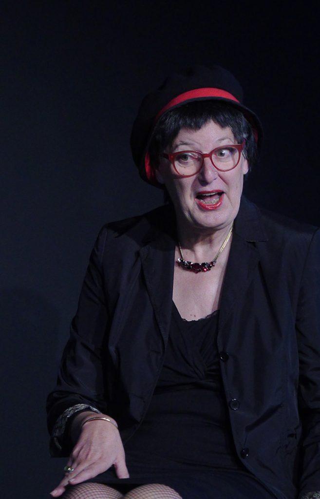 Ein Frau sitz auf einem Stuhl. Sie ist schwarz gekleidet und trägt einen Hut mit einem roten Band.