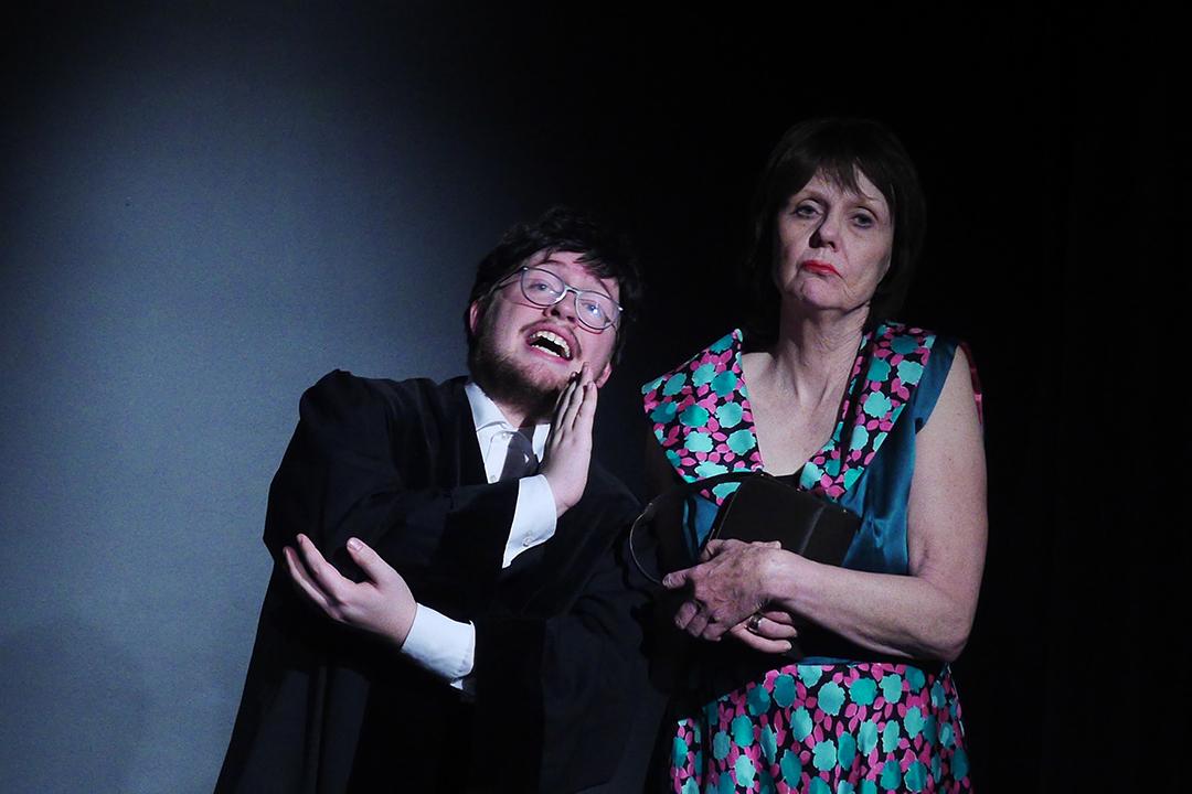 Links ein junger Mann in Anwaltsrobe, rechts eine ältere Dame im bunten Seidenkleid. Er erzählt ihr etwas mit vor gehaltener Hand. Sie ist offensichtlich davon nicht angetan. Sie sind auf einer schwarzen Bühne.