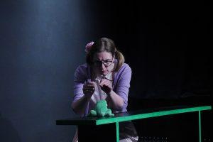 Eine Schauspielerin kniet vor einer Bank mit grünem Rand. Darauf sitzt ein grüner Frosch aus Plüsch. Sie spielt ein kleines Mädchen, die dem Frosch etwas erzählt.