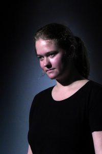 Eine junge FRau vor schwarzem Hintergrund. Eine Portraitaufnahme