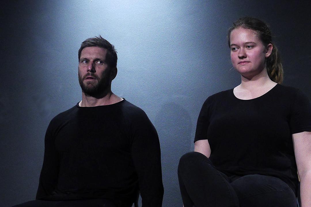 Zwei Teilnehmer in schwarzer Übungskleidung sitzen auf einer Bank auf der Bühne. Links ein junger Mann mit fragendem Gesicht und rechts von ihm eine junge Frau mit blondem Pferdeschwanz. Sie hört ihm aufmerksam zu.