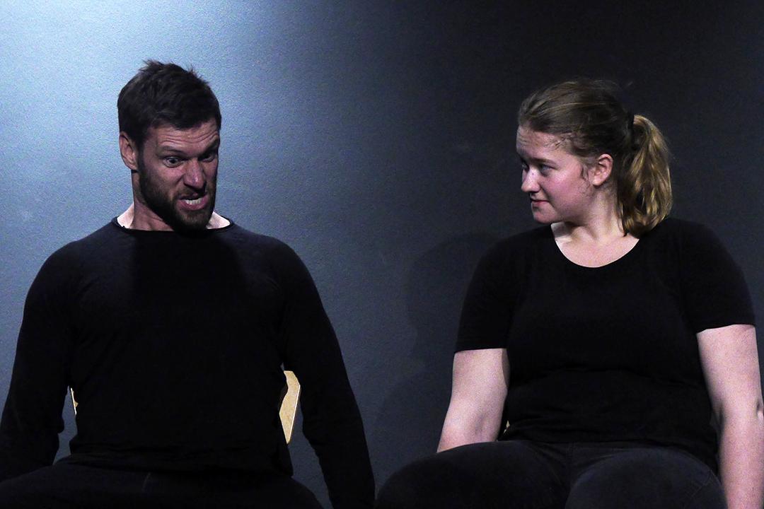 Zwei Teilnehmer in schwarzer Übungskleidung sitzen auf einer Bank auf der Bühne. Links ein junger Mann mit starker Mimik und rechts von ihm eine junge Frau mit blondem Pferdeschwanz. Sie hört ihm aufmerksam zu.
