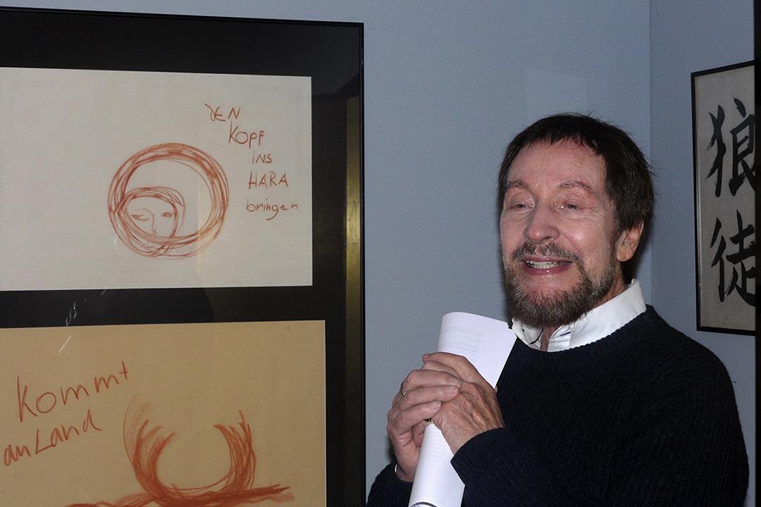 """Wolfgang Keuter spricht über Slow Acting. Er trägt einen dunklen Pulli und ein weißes Hemd und steht im Studienraum. Links im Bild sind zwei Zeichnungen, auf der einen ist ein Gesicht zuerkennen, rechts davon steht """"Den Kopf ins Hara bringen."""" zu sehen."""