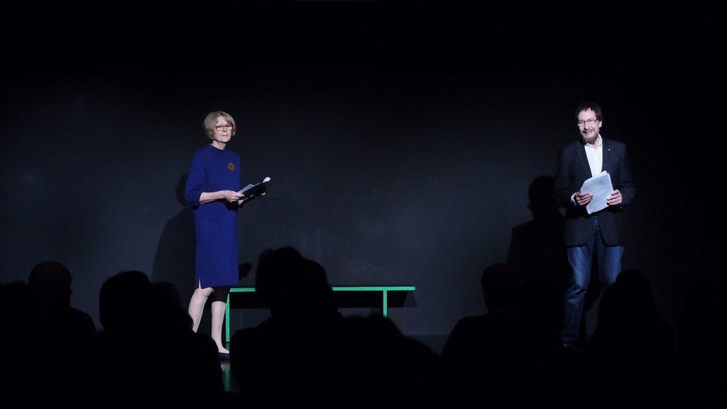 Sigrid Abendroth trägt ein blaues Kleid mit goldener Brosche, Wolfgang ein weißes Hemd und einen dunklen Blazer. Beide sind auf der Bühne und haben das Manuskript der dialogischen Lesung von Effi Briest in der Hand.