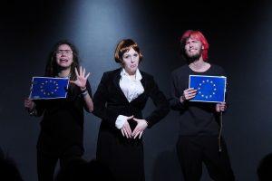 Drei Schüler zeigen eine Szene aus ihrem Programm Kabarettungsdienst KLIMAX. In der Mitte wird die Kanzlerin und links und rechts von ihr werden Europapolitiker karikiert.