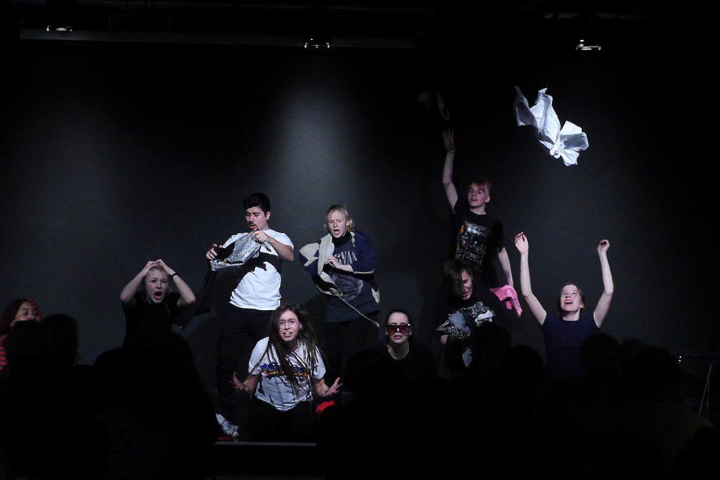 Neun Schüler zeigen eine Szene aus ihrem Programm Kabarettungsdienst KLIMAX. Das Thema ist der übermäßige Konsum von Kleidung. Viele Kleidungsstücke fliegen in hohem Bogen durch den Raum.