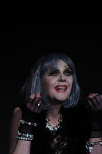 """Sigrid Abendroth als """"Claudia"""", eine alternde Diva. sie schaut freudig ins Scheinwerferlicht. Großes Bühnenmakeup, lange Wimpern und eine silbergraue Perücke"""