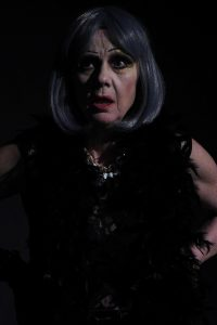 Eine stark geschminkte Schauspielerin zeigt einen entsetzten Gesichtsausdruck. Sie trägt starkes Bühnenmakeup