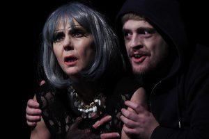 """Sigrid Abendroth als """"Claudia"""", eine alternde Diva mit großem Bühnenmakeup, lange Wimpern und eine silbergraue Perücke. Sie schaut fragend ins Scheinwerferlicht. Hinter ihr ist die Figur des Todes in der Gestalt eines Stalkers zu sehen. Er trägt einen Kapuzenpulli in scharz und zhat ein blasses Gesciht mit kräftigen Augenrändern. Maecl spielt hier die Figur des Todes."""