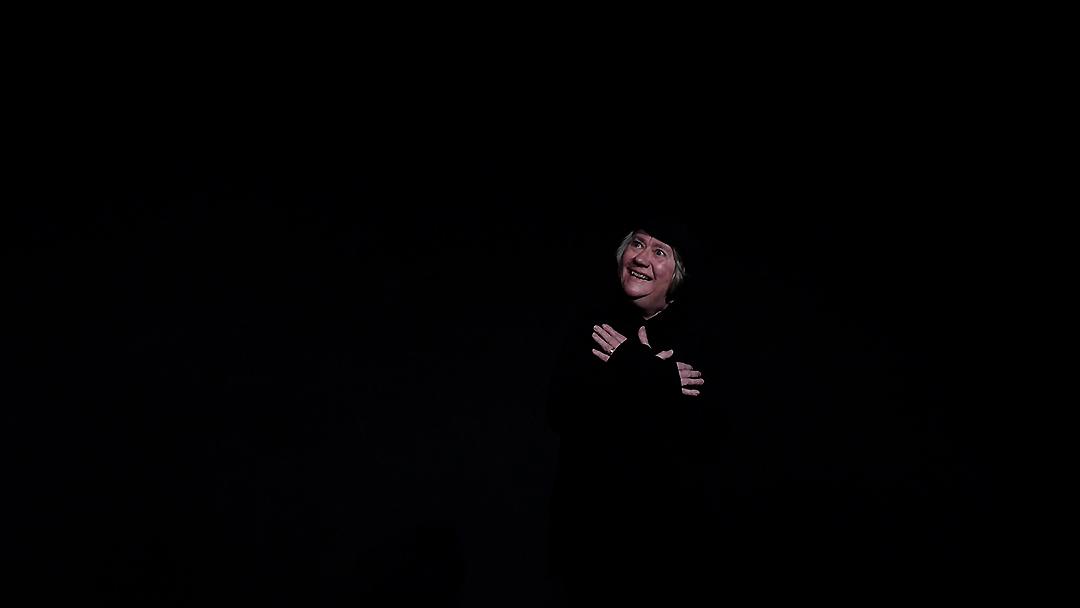 Eine ältere Frau sitzt auf einem Stuhl und schaut heiter in die obere Ecke des schwarzen Bühnenraums
