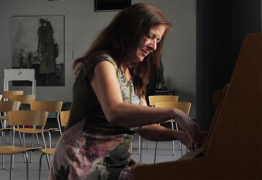 Sybille Karasch sitzt in einem blumigen Sommerkleid am neu gestimmten Klavier auf der Bühne Campus Goolzheim