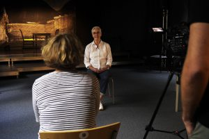 Antje Orentat beim Interview, sie sitz auf einem Stuhl. Im Hintergund die Bühne des TheaterLabor TraumGesciht.