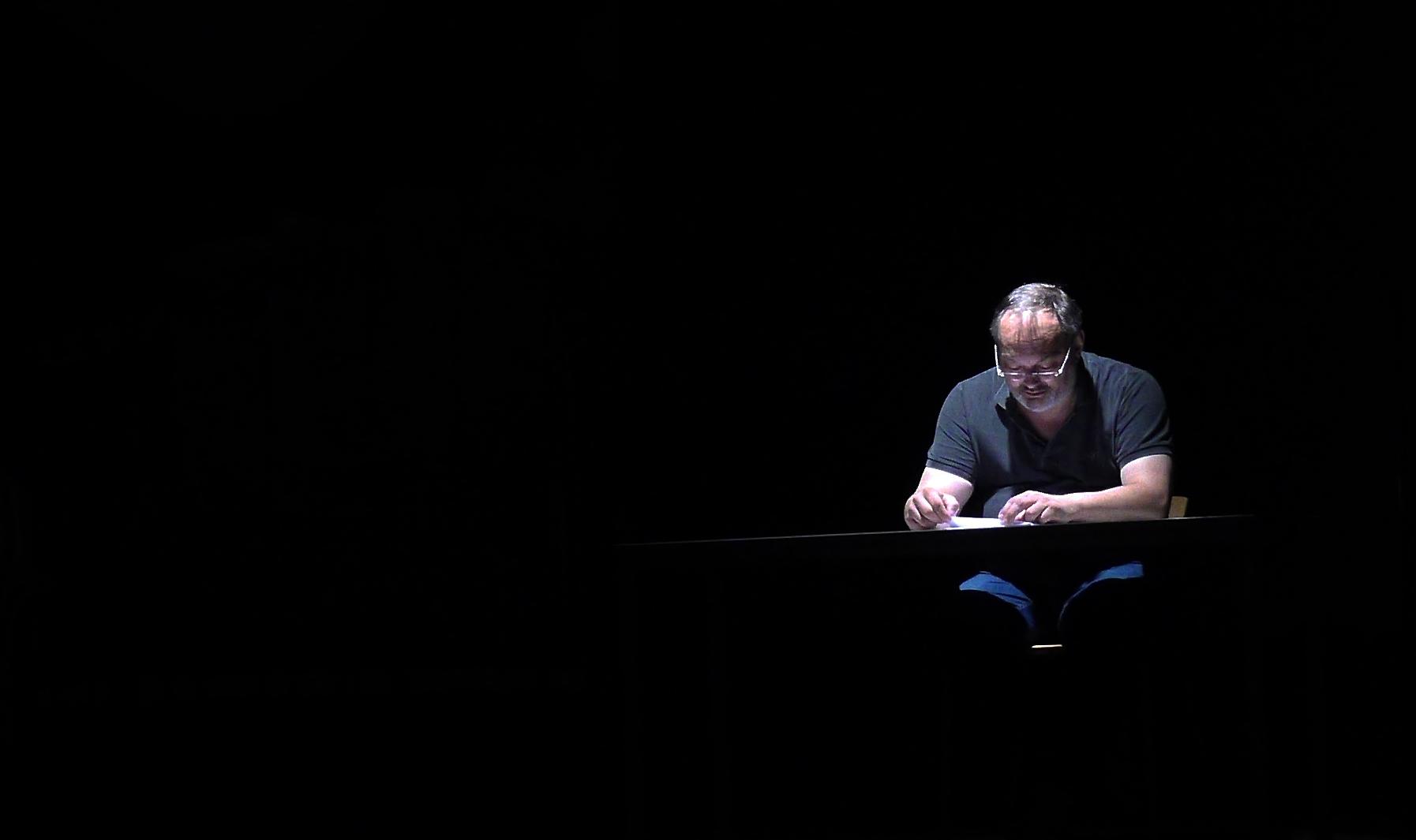 Ein Mann sitzt auf der schwarzen Bühne auf einem Stuhl hinter eionem schwarzen Tisch und liest.
