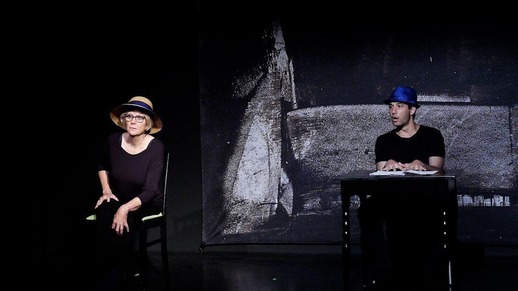 Links sitzt die Mutter, mit einem Strohhut schaut sie griesgrämig nach links oben. Am Tisch sitzt der Sohn mit einem blauen Hut und ist über etwas erstaunt.