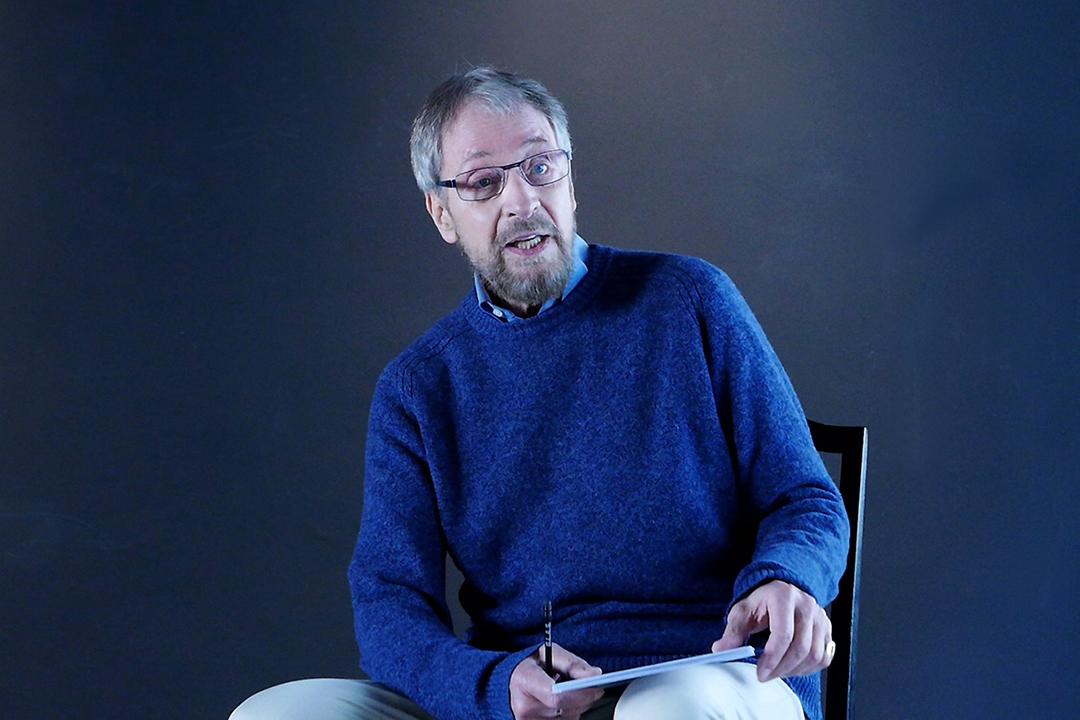 Wolfgang Keuter sitzt auf ewinem Stuhl. Er trägt einen blauen Pulli und eine helle Hose.