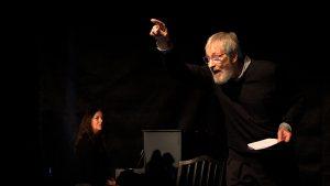 Schwarzer Bühnenraum. Links sitzt Sybile Karrasch am schwarzen Klavier. Rechts von ihr steht Wolfgang Keuter und spricht mit starker Mimik und klarer Zeigegebärde einen Text von Hölderlin.