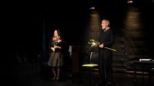 Schwarzer Bühnenraum. Links steht Sybile Karrasch, rechts Wolfgang Keuter. Beide haben eine Lilie als Geschenk erhalten und nehmen freudestrahlend ihren Applaus entgegen.